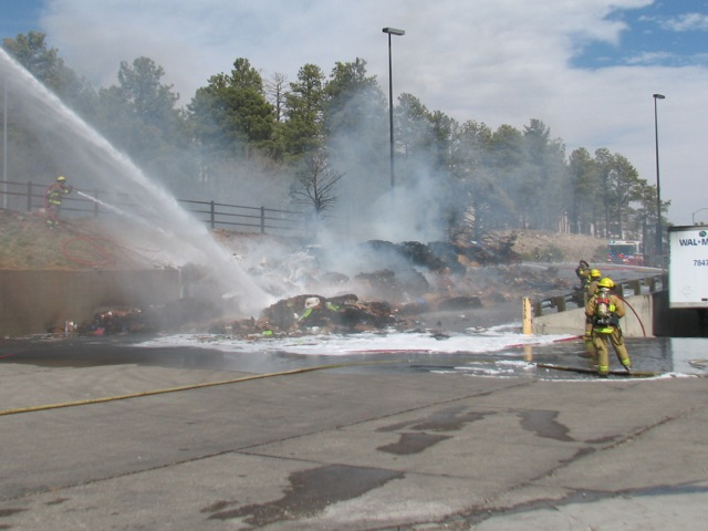 Firefighters spray streams of water and foam on the pile of compressed cardboard which caught on fire Sunday afternoon. (Photo: Kyle Anderson/NAZ Today)