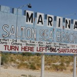 A roadside sign for the Salton Sea Beach and Marina. The path between Highway 86 and the beach was filled with trailer homes built up like actual homes with yards, fences, garages, etc.